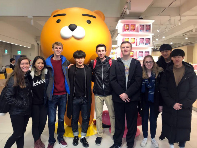 Miami and Korean students pose by cartoon bear statue
