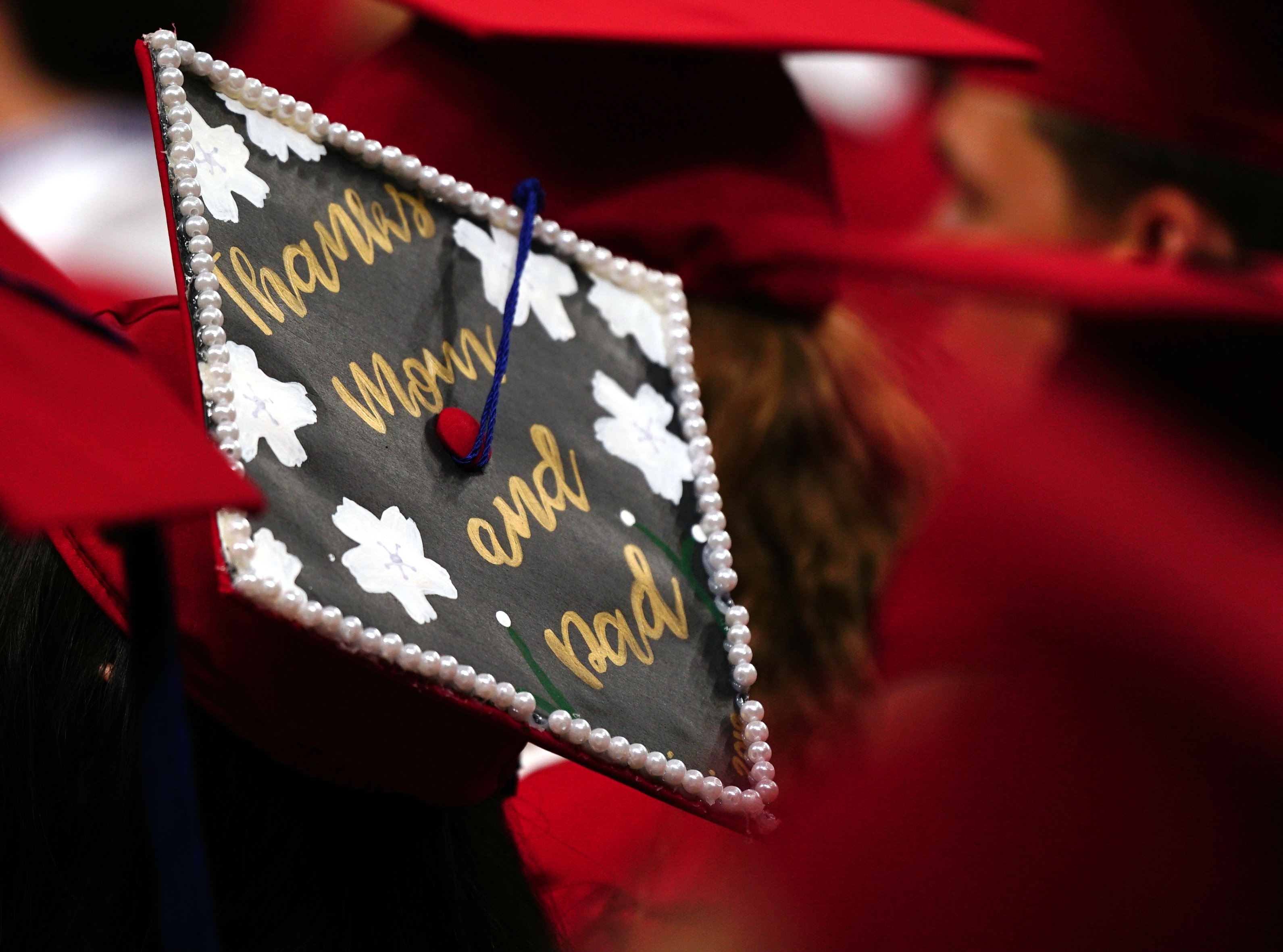 A graduate holds up her diploma cover for a photo
