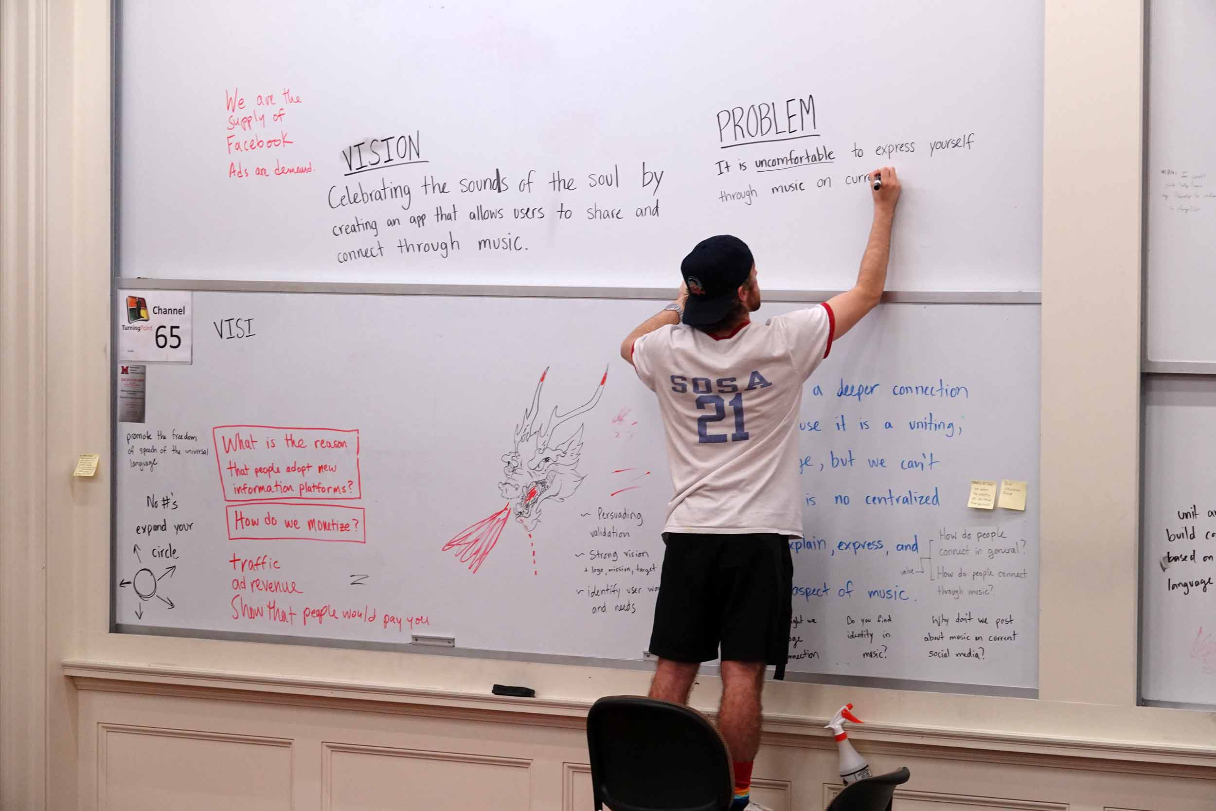 Student works out ideas on a whiteboard